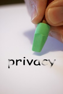 """A picture of a hand holding a pencil eracer over the word """"privacy"""" with the word slightly erased."""