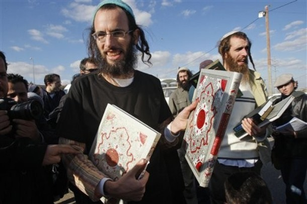 Israeli Orthodox Jewish men hold copies of the Quran, after Jewish settlers vandalized the local mosque