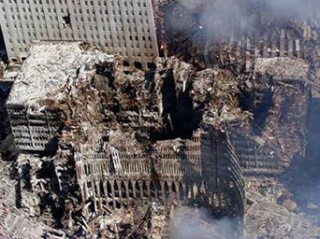 An aerial view on September 17th, 2001 shows only a small portion of the scene where the World Trade Center collapsed following the supposed Sept. 11 terrorist attack. Surrounding buildings were obviously heavily damaged by the scattered debris and massive force of the imploding twin towers ~ before DOJ head and future Director of Homeland Security, Michael Chertoff retained and destroyed all the evidence from this clearly evident, but never declared crime scene. (U.S. Navy photo by Chief Photographer's Mate Eric J. Tilford)