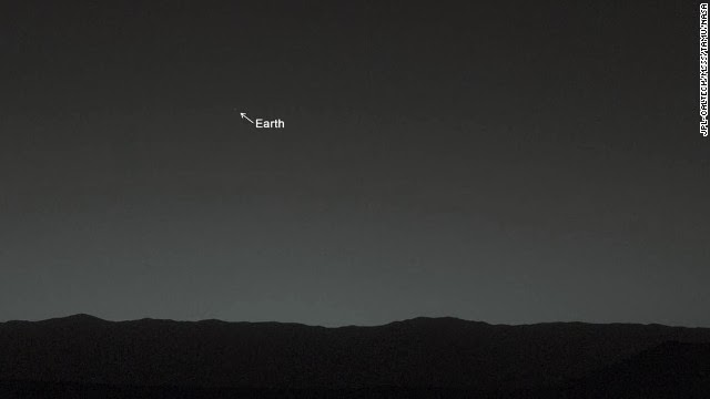 """This view of the twilight sky and Martian horizon, taken by NASA's Mars rover Curiosity, includes Earth as the brightest point of light in the night sky. Earth is a little left of center in the image, and our moon is just below Earth. A human observer with normal vision, if standing on Mars, could easily see Earth and the moon as two distinct, bright """"evening stars."""""""