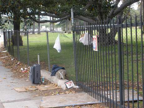 Homeless Veteran outside the front fence that secures Donna Beiter's mansion so she can live in luxury and safety.