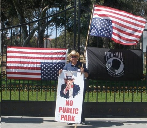 """Rees Lloyd, former Commander of District 21 and """"legal advisor"""" to the American Legion holds an upside down American Flag in front of the Los Angeles VA during a past protest rally."""