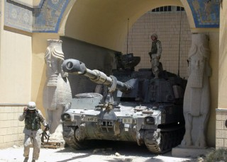 A US soldier stands on a Bradley tank stationed at the main entrance of the Iraqi National Museum as another soldier walks by in Baghdad 21 June 2003