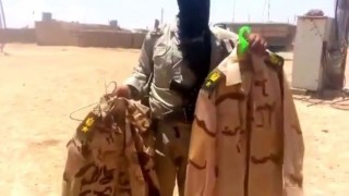Armed member of ISIL holding up Iraqi soldier uniforms before tossing them on the ground-Mosul, Iraq (June, 11, 2014)