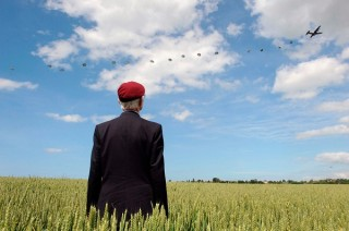 British World War II veteran Frederick Glover poses for a photograph as soldiers parachute during a D-Day commemoration in Ranville, France, June 5, 2014