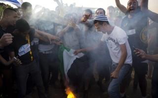 Settler protestors burning a Palestinian flag