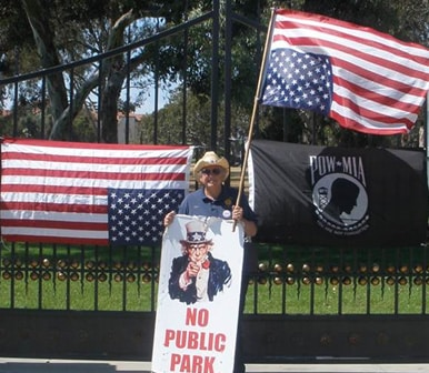 American Legionnaire Rees Lloyd holding a flipped American Flag in protest  of the VA's misappropriation of land and the mistreatment of homeless Veterans