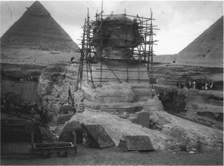The Great Sphinx, with the restoration scaffolding of Emile Baraize, looking northwest, December 26, 1925. The pyramids of Khufu (right) and Khafre (left) are in the background.