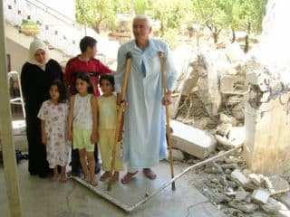A Palestinian family standing in the ruins of their house in the West Bank which Israeli forces have just demolished in July 2005